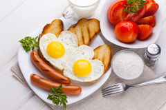 Breakfast on Valentine`s Day - fried eggs in the shape of a heart and sausages. Top view Royalty Free Stock Photo
