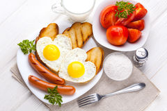 Breakfast on Valentine`s Day - fried eggs in the shape of a heart and sausages. Top view Stock Images