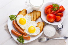 Breakfast on Valentine`s Day - fried eggs in the shape of a heart and sausages. Top view Stock Image