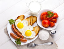 Breakfast on Valentine`s Day - fried eggs in the shape of a heart and sausages. Top view Royalty Free Stock Photography