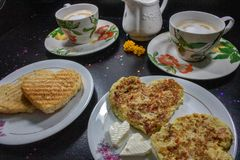 Breakfast on Valentine`s Day - fried omelete, bread, apple and White cheese in the shape of a heart coffe and milk. NRomantic Day royalty free stock images