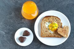 Breakfast on Valentine`s Day. Breakfast Valentine`s Day. On the plate is toast with fried eggs ine a heart and orange juice Stock Image