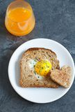 Breakfast on Valentine`s Day. Breakfast Valentine`s Day. On the plate is toast with fried eggs inside a heart and orange juice Stock Photos