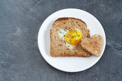 Breakfast on Valentine`s Day. Breakfast Valentine`s Day. On the plate is toast with fried eggs inside a heart and orange juice Royalty Free Stock Photos