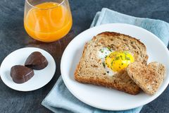 Breakfast on Valentine`s Day. Breakfast Valentine`s Day. On the plate is toast with fried eggs inside a heart and orange juice Stock Images