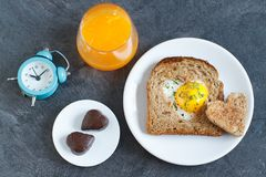 Breakfast on Valentine`s Day. Breakfast Valentine`s Day. On the plate is toast with fried eggs inside a heart and orange juice Stock Image