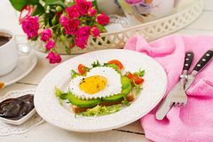 Breakfast on Valentine`s Day - sandwich of fried egg in the shape of a heart, avocado and fresh vegetables. Royalty Free Stock Photography