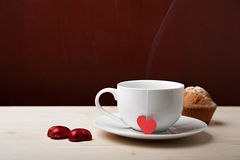 Breakfast on valentine's day. On a wooden table a cup costs with hot by drink of candy and cake Royalty Free Stock Images