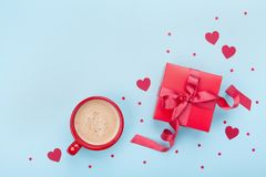 Breakfast for Valentines day. Coffee, gift box, paper heart and confetti on blue background top view. Empty space for text. Stock Image