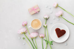 Breakfast for Valentines day with cup of coffee, gift, flowers and cake in shape of heart on gray table from above. Stock Image