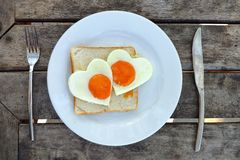 Breakfast for Valentines day. Fried eggs in the shape of a heart at toast on white plate and wooden table. Knife and fork lie. Nearby stock image