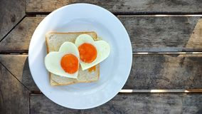 Breakfast for Valentines day with love. Fried eggs in the shape of a heart at toast on white plate and wooden table on the beach.  royalty free stock photography