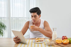 Breakfast. Vietnamese handsome man having breakfast and watching something on tablet computer Stock Photography