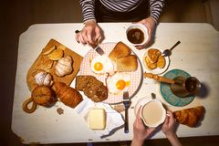 Breakfast, view from the top.Toast, coffee, fried eggs. Hands of two girls Stock Photography
