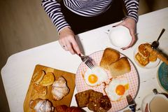 Breakfast, view from the top.Toast, coffee, fried eggs. Hands of two girls Royalty Free Stock Photos