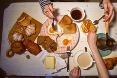 Breakfast, view from the top.Toast, coffee, fried eggs. Hands of two girls Stock Photos