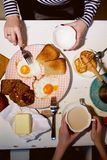 Breakfast, view from the top.Toast, coffee, fried eggs. Hands of two girls Royalty Free Stock Image