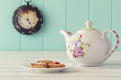 Breakfast vintage. Tea Time. A teapot, a plate with some german cookies and a clock in the background. Five o'clock. Tea time. Robin egg blue background. Vintage Royalty Free Stock Photo