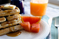 Breakfast of waffles. Breakfast plate of fresh waffles with syrup and fruit Royalty Free Stock Photo