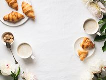Breakfast on white flat lay with coffee and croissants. Breakfast on white flat lay. Croissants with cup of coffee and flowers royalty free stock images