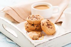 Breakfast on white retro wooden salver with whole and bitten chocolate chips cookies with cup of coffee with milk. royalty free stock image