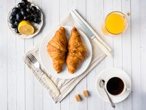 Breakfast on a White Table Coffee Croissant Orange juice Grapes Apple Chocolate.  Royalty Free Stock Photography