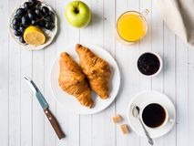 Breakfast on a White Table Coffee Croissant Orange juice Grapes Apple Chocolate.  Stock Photos
