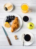 Breakfast on a White Table Coffee Croissant Orange juice Grapes Apple Chocolate.  Stock Image