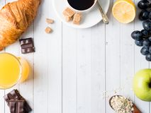 Breakfast on a White Table Coffee Croissant Orange juice Grapes Apple Chocolate Copy Space for Text. Breakfast on a White Table Coffee Croissant Orange juice Royalty Free Stock Image