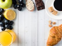 Breakfast on a White Table Coffee Croissant Orange juice Grapes Apple Chocolate Copy Space for Text. Breakfast on a White Table Coffee Croissant Orange juice Stock Photos