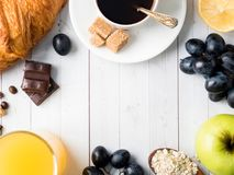 Breakfast on a White Table Coffee Croissant Orange juice Grapes Apple Chocolate Copy Space for Text. Breakfast on a White Table Coffee Croissant Orange juice Stock Image