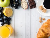 Breakfast on a White Table Coffee Croissant Orange juice Grapes Apple Chocolate Copy Space for Text. Breakfast on a White Table Coffee Croissant Orange juice Stock Photo