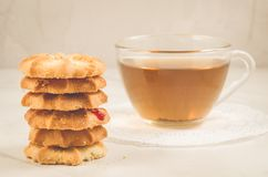 Breakfast whith cookies and glass cup whith tea/Breakfast whith cookies and glass cup whith tea on a white table. Focus on cookies. Sweet hot pastry food bakery stock photography