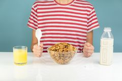 Breakfast with whole grain cereals, milk and juice. Illustrative. Minimalistic image of healthy vegetarian food on the table and hungry person royalty free stock photos
