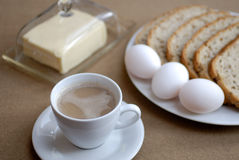 Breakfast wit butter. Lovely breakfast with coffe, three eggs, bread and butter Royalty Free Stock Images