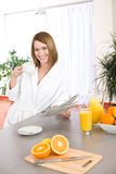 Breakfast - woman with newspaper in kitchen Royalty Free Stock Photos