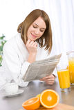 Breakfast - woman reading newspaper in kitchen Stock Images