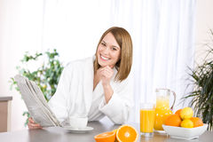 Breakfast - woman reading newspaper in kitchen Stock Photos