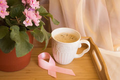 Breakfast for women - pink ribbon awareness symbol breast cancer. Coffee Cup on a wooden tray and pink violet Stock Image
