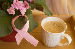 Breakfast for women - pink ribbon awareness symbol breast cancer. Coffee Cup on a wooden tray and pink violet Stock Photo