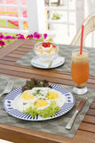 Breakfast on the wooden table: sunny side up eggs and cream chee Stock Photos