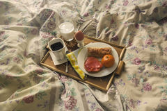 Breakfast on a wooden tray on a bed Royalty Free Stock Images