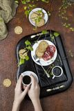 Breakfast on a wooden tray. Coffee, crackers and salami Stock Photography