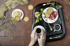 Breakfast on a wooden tray. Coffee, crackers and salami Royalty Free Stock Images