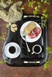 Breakfast on a wooden tray. Coffee, crackers and salami Stock Image