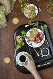Breakfast on a wooden tray. Coffee, crackers and salami Stock Photos
