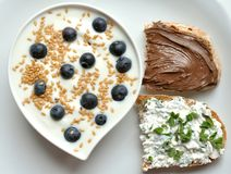 Breakfast with yogurt, blueberry and flax seeds. And sandwiches with cheese and Nutella chocolate . healthy breakfast concept . good morning habit royalty free stock photos