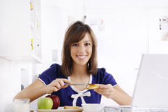 Breakfast of young woman. Young woman in breakfast, eating and using laptop Stock Image