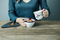 Breakfast. Young woman pouring milk into cereal for breakfast on wooden table Stock Photography