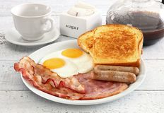 Breakfst plate of ham and eggs. Ham and eggs and sausages on white plate on white table Stock Photos